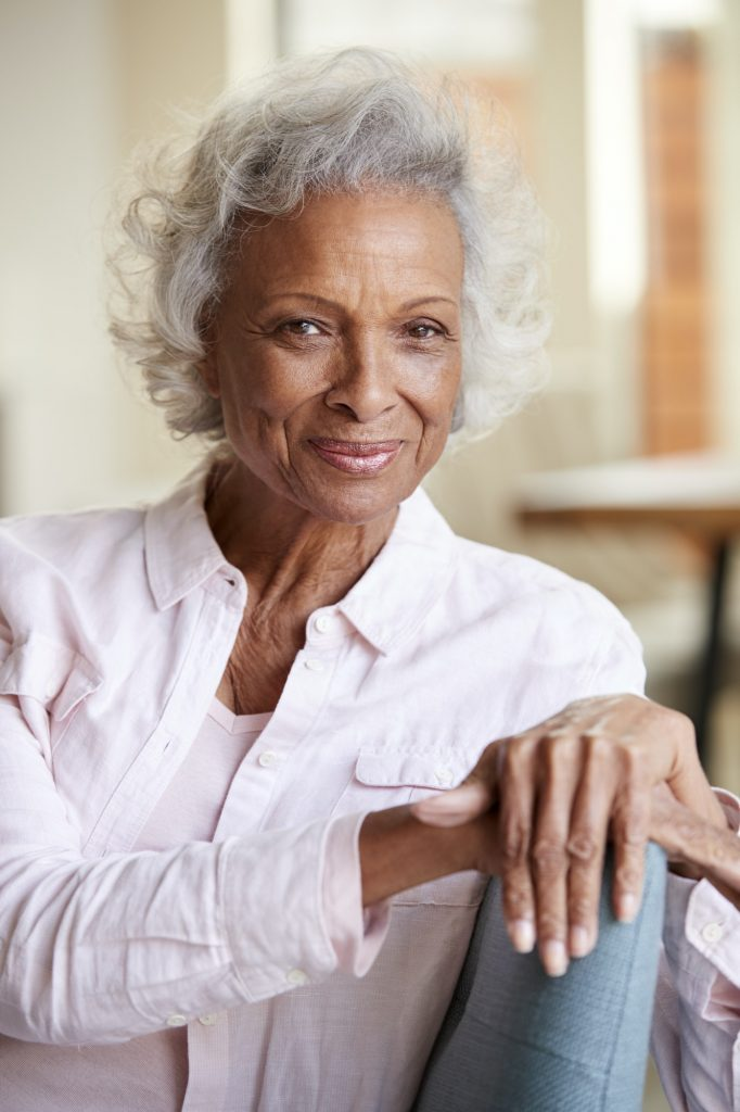 Portrait Of Smiling Senior Woman Relaxing On Sofa At Home