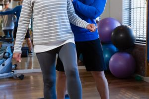 Physiotherapist assisting senior woman in performing exercise on foam roll