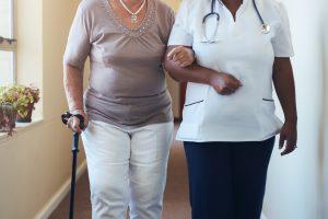 Senior woman walking being helped by female nurse